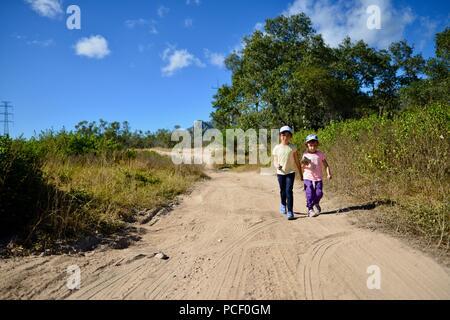 Two children walk down a dry dusty dirt road, Townsville, Queensland, Australia - Stock Photo