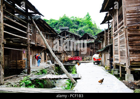 Typical Dong Village,Wooden Houses,Huanggang Dong Village,Dong Costumed Girls,Singing to Students,,Dwellings,Guizjou,PRC,People's Republic of China - Stock Photo