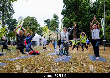 Police join a Yoga Class at WOMAD on Sunday 29 July 2018 held at Charlton Park, Wiltshire . Pictured: 2 Police officers of the Wiltshire Police Force joined in a free Yoga Class taking place in the World of Wellbeing . - Stock Photo