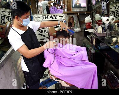 ANTIPOLO CITY, PHILIPPINES - JULY 30, 2018: A barber cuts the hair of a young cutomer in his barber's shop. - Stock Photo