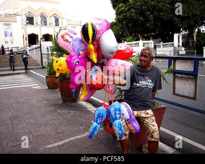 ANTIPOLO CITY, PHILIPPINES - JULY 30, 2018: A man sells assorted toy balloons outside of the popular tourist destination Our Lady of Peace and Good Vo - Stock Photo