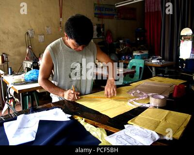 ANTIPOLO CITY, PHILIPPINES - JULY 30, 2018: A tailor creates a pattern for a dress at his tailoring shop. - Stock Photo