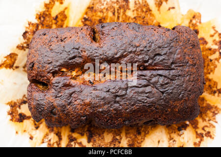 Homemade vegan baked banana bread on parchment paper just out of the oven - Stock Photo
