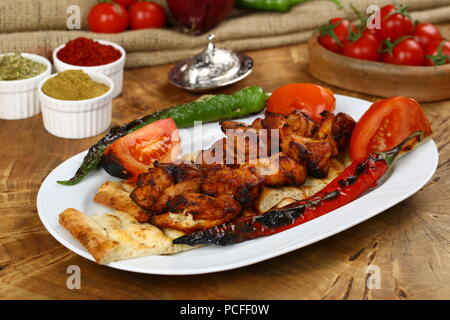 Skewers of grilled chicken on plate with garnish - Stock Photo