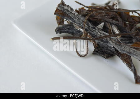 Detail top view of dried seaweed:  wakame. Isolated on white.Nutrient rich vegan, raw and healthy sea vegetables.