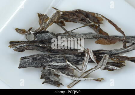 Detail top view of dried seaweed:  wakame. Isolated on white.Nutrient rich vegan, raw and healthy sea vegetables. - Stock Photo