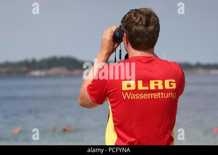 ILLUSTRATION - 02 August 2018, Germany, Eckernfoerde: Vincent Schmette, lifeguard of the 'Deutsche Lebens-Rettungs-Gesellschaft' (lit. German Lifesaving Association) (DLRG), observes what is happening on the beach. Photo: Bodo Marks/dpa - Stock Photo