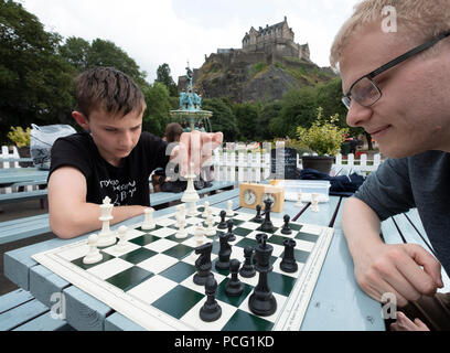 Edinburgh, Scotland, UK. 2 August, 2108. Public chess games in cafe in Princes Street Gardens at foot of Edinburgh Castle. James Hartman(L) and Andrew McHarg play chess on tables provided for the public and local chess clubs. They meet every Thursday and Sunday in summer. Credit: Iain Masterton/Alamy Live News - Stock Photo