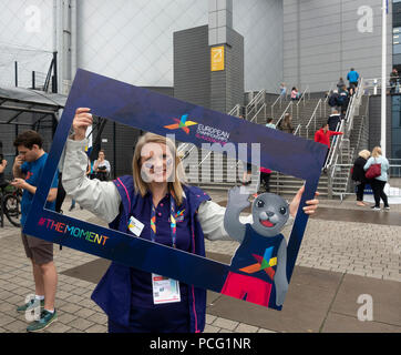 Glasgow, Scotland, UK. 02nd August, 2018. A smiling volunteer posing for a Sealfie inside a frame featuring the Games mascot Bonnie the Seal, outside the Sir Chris Hoy Velodrome (Emirates Arena) in the Dalmarnock area of Glasgow before the first cycling events of the Glasgow 2018, a multi-sport event. Most of the sports will be hosted in Scotland, with the Velodrome hosting the Track Cycling events. Credit: Elizabeth Leyden/Alamy Live News - Stock Photo