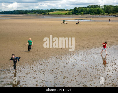 Cramond, Edinburgh, Scotland, United Kingdom, 2nd August 2018. Boys running on the wet sand at low tide on the beach at Cramond with dog walkers in the distance - Stock Photo