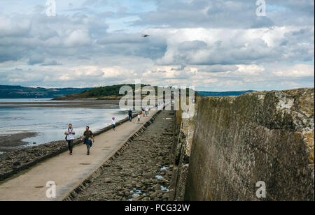 Cramond, Edinburgh, Scotland, United Kingdom, 2nd August 2018. People walking on the tidal causeway to Cramond Island with the concrete World War II barrier - Stock Photo