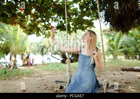 Young pretty girl riding swing and making selfie by smartphone, sand and trees in background. - Stock Photo