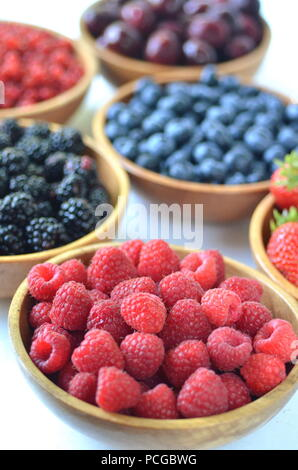 Detail of fresh summer fruit, berries. Strawberries, raspberries, cherries, blackberries, blueberries and red currants in wooden bowls - Stock Photo