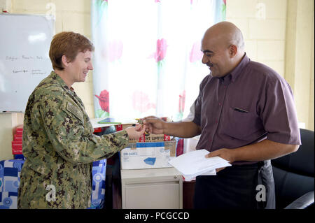 TARAWA, Kiribati (May 25, 2015) Lead Medical Planner Lt. Cmdr. Tammy Servies from Hammond, Ind., and currently assigned to the Navy Environmental and Preventive Medicine Unit 6 (NEPMU-6) gives a command coin to Dr. Alani Tangitau, the intern coordinator at the Tungaru Central Hospital in Tarawa, during a visit to the hospital to discuss upcoming event that will take place during Pacific Partnership 2015.  Now in its tenth iteration, Pacific Partnership is the largest annual multilateral humanitarian assistance and disaster relief preparedness mission conducted in the Indo-Asia-Pacific region.  - Stock Photo