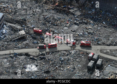 Japan (March 18, 2011) An aerial view of Japanese Ground Self-Defense Force personnel and disaster relief crews searching Sukuiso, Japan for victims of a 9.0-magnitude earthquake and subsequent tsunami. - Stock Photo