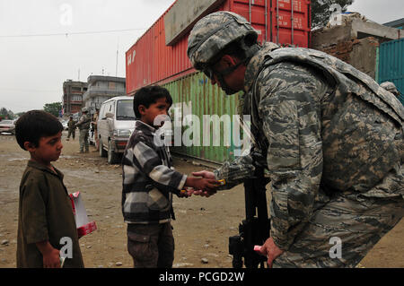Lt. Col. Kevin Yandura, a NATO Air Training Command - Afghanistan advisor, talks with two young Afghan children during a humanitarian assistance mission. ( - Stock Photo