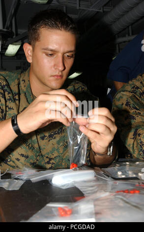 Aboard USS Tarawa (LHA 1), hospital corpsman Beau Surratt, attached to Battalion Landing Team, 1st Battalion, 5th Marines, 11th Marine Expeditionary Unit, fills plastic packets with iron tablets for the people of Bangladesh. (Iron is taken to prevent anemia, the inability of blood to properly clot, caused by malnutrition). Amphibious assault ship Tarawa and embarked 11th Marine Expeditionary Unit are conducting humanitarian assistance/disaster relief efforts in response to the government of Bangladesh's request for assistance after Tropical Cyclone Sidr struck their southern coast Nov. 15. The