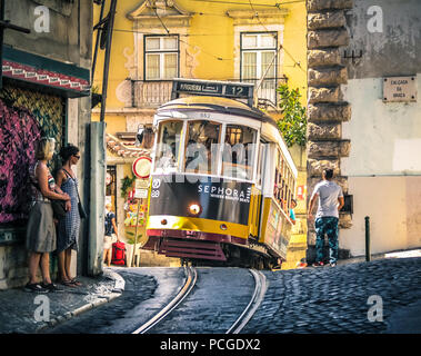 Lisbon. Famous old tram climbing uphill in Alfama. - Stock Photo
