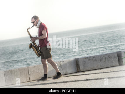 Lisbon. Saxophone player by the Targus river. - Stock Photo