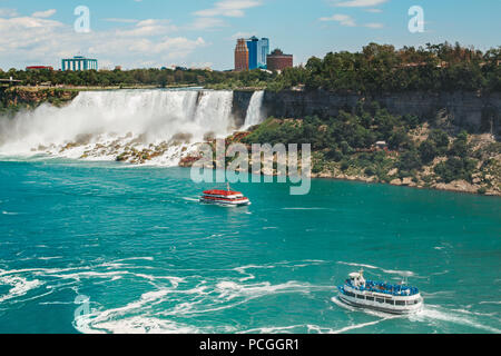 Aerial top landscape view of Niagara Falls. Two tour excursion boats meet in river water on border between US and Canada. Famous Canadian waterfal tou - Stock Photo
