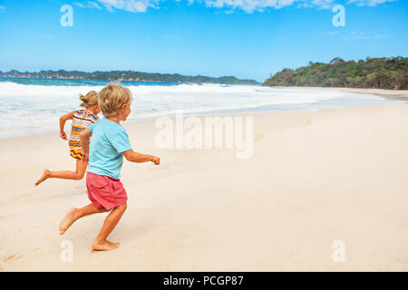 Happy barefoot kids have fun on beach walk. Run and jump by white sand along sea surf. Family travel lifestyle, outdoor sports activities and games. - Stock Photo