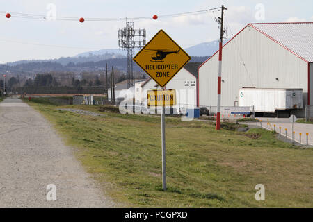 A yellow sign on a trail indicating helicopter zone with over head wires with orange balls suspended on them in the background - Stock Photo