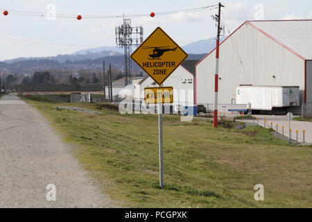 A yellow sign indicating a helicopter zone with caution underneath. - Stock Photo