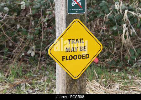 A yellow trail may flood sign on a post - Stock Photo