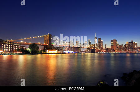 Panorama of Brooklyn Bridge and New York City (Lower Manhattan) with lights and reflections at dusk, USA - Stock Photo