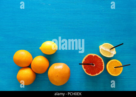 Raw food slicing and whole citrus fruit orange lemon grapefruit View from above fruits on a wooden board and blue background - Stock Photo