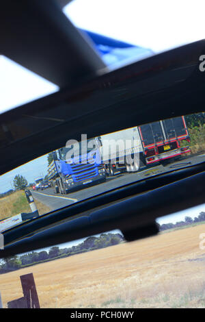 lorry travelling on dual carriageway reflected in vehicle rear view mirror uk - Stock Photo