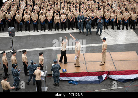 PACIFIC OCEAN (May 30, 2017) A newly frocked petty officer reaches to high five Command Master Chief Spike Call during a frocking ceremony on the flight deck of the aircraft carrier USS Theodore Roosevelt (CVN 71). Theodore Roosevelt is currently moored pier side in her homeport of San Diego after recently completing Tailored Ship's Training Availability and Final Evaluation Problem (TSTA/FEP). - Stock Photo