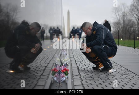 WASHINGTON (April 9, 2018) Master-at-Arms 1st Class Ian Barton, one of four finalists for Navy Reserve Sailor of the Year, reads a note left at the Vietnam Veterans Memorial during a run at the National Mall. The run is the first event in a week-long selection board to select the top reserve component Sailor and recognize each finalist for their exceptional performance. - Stock Photo