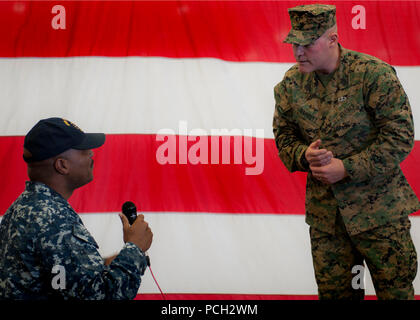 """SAN DIEGO (Jan. 5, 2015) Sgt. Major of the Marine Corps Micheal P. Barrett takes a question from Chief Hospital Corpsman Gerald Lee during an all-hands call aboard the amphibious assault ship USS America (LHA 6). America is the first ship of its class and the fourth to bear the name. The ship replaces the Tarawa-class of amphibious assault ship as the next generation """"big-deck"""" amphibious assault ship and is optimized for aviation and capable of supporting current and future aircraft such as the MV-22 Osprey and F-35B Joint Strike Fighter. - Stock Photo"""