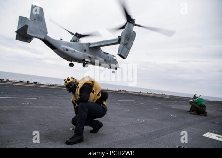 """EAST CHINA SEA (March 16, 2017) Aviation Boatswain's Mate (Handling) 3rd Class Jesse Harris, assigned to amphibious assault ship USS Bonhomme Richard (LHD 6), braces himself as an MV-22B Osprey, assigned to the """"Flying Tigers"""" of Marine Medium Tiltrotor Squadron (VMM) 262, takes off during an air assault exercise. Bonhomme Richard is on a routine patrol operating in the Indo-Asia-Pacific region to enhance warfighting readiness and posture forward as a ready-response force for any type of contingency. - Stock Photo"""