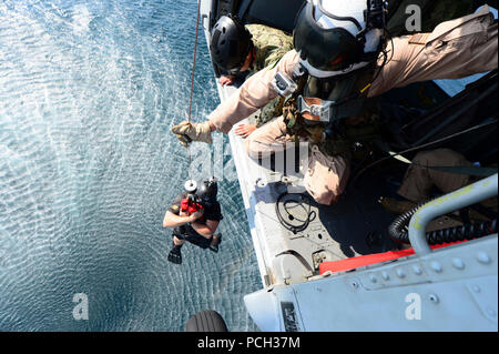 U.S. 5TH FLEET AREA OF RESPONSIBILITY (Nov. 6, 2012) Explosive Ordnance Disposal Technician 3rd Class Jake Sleight, assigned to Explosive Ordinance Disposal Mobile Unit (EODMU) 1, is hoisted into a helicopter by Naval Air Crewman 3rd class Alexander Lantry, assigned to Helicopter Sea Combat Squadron (HSC) 26, during a training exercise. EODMU 1 is deployed with Commander, Task Group (CTG) 56.1, providing support for maritime security operations and theater security cooperation efforts in the U.S. 5th Fleet area of responsibility. - Stock Photo