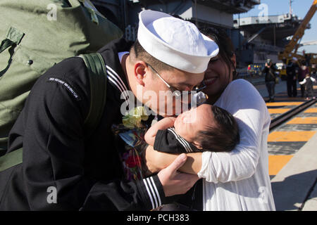 YOKOSUKA, Japan (Nov. 20, 2012) Aviation Electronics Technician 2nd Class Richard Ching, from Honolulu, kisses his son after the aircraft carrier USS George Washington (CVN 73) returned to Yokosuka, Japan. George Washington and embarked Carrier Air Wing (CVW) 5 provide a combat-ready force that protects and defends the collective maritime interest of the U.S. and its allies and partners in the Asia-Pacific region. - Stock Photo