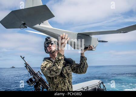 PACIFIC OCEAN (May 9, 2018) Operations Specialist 3rd Class Neil Wierboski, assigned to Coastal Riverine Squadron (CRS) 3, prepares the unmamned aerial vehicle for launch aboard a Mark VI patrol boat during unit level training conducted by Coastal Riverine Group (CRG) 1's Training and Evaluation Unit. CRG-1 provides a core capability to defend designated high value assets throughout the green and blue-water environment and providing deployable adaptive force packages worldwide in an integrated, joint and combined theater of operations. - Stock Photo