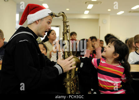 YOKOSUKA, Japan (Dec. 3, 2012) Musician 3rd Class Brandon Kies, a member of the U.S. 7th Fleet Far East Edition Brass Band, shows a child his saxophone during a Christmas music performance at The Sullivans Elementary School at Command Fleet Activities, Yokosuka. The band performed music at several locations throughout the day including the Child Development Center and outside the Navy Exchange. - Stock Photo