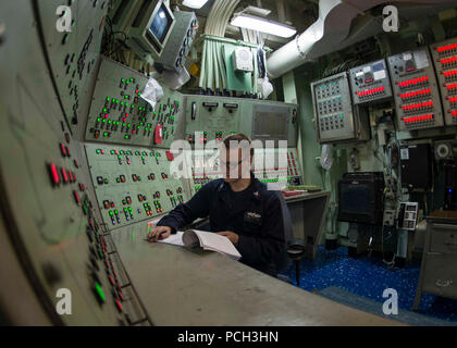 U.S. 5TH FLEET AREA OF OPERATIONS (May 12, 2018) Damage Controlman 2nd Class Ross Fergerson stands watch as the damage control central watch supervisor aboard the Wasp-class amphibious assault ship USS Iwo Jima (LHD 7). Iwo Jima is homeported in Mayport, Fla., and is on deployment to the U.S. 5th Fleet area of operations in support of maritime security operations to reassure allies and partners, and preserve the freedom of navigation and the free flow of commerce in the region. - Stock Photo