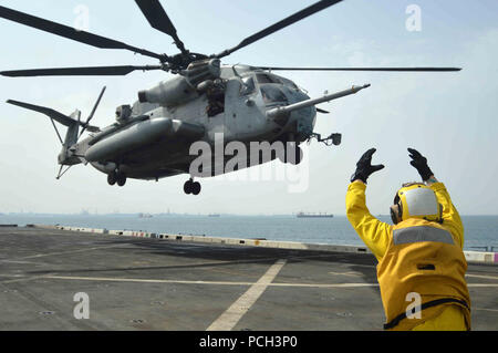 GULF OF OMAN (April 18, 2013) Aviation Support Equipment Technician 2nd Class Ryan Snay signals take-off to a CH-53E Super Stallion during flight operations aboard the amphibious transport dock ship USS San Antonio (LPD 17). San Antonio is deployed as part of the Kearsarge Amphibious Ready Group with embarked Marines from the 26th Marine Expeditionary Unit, which is on a scheduled deployment supporting maritime security cooperation efforts in the U.S. 5th Fleet area of responsibility. - Stock Photo