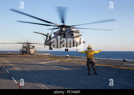 A U.S. Sailor directs a Marine Corps CH-53E Super Stallion helicopter to take off from the amphibious assault ship USS Kearsarge (LHD 3) in the Atlantic Ocean Sept. 21, 2014. The Kearsarge was underway conducting sea trials. - Stock Photo