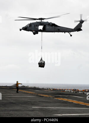 A U.S. Sailor signals to an MH-60 Seahawk helicopter as it delivers supplies on the flight deck aboard the amphibious assault ship USS Boxer (LHD 4) during a vertical replenishment with the Military Sealift Command fleet replenishment oiler USNS Rappahannock (T-AO 204) in the Pacific Ocean March 17, 2011. Boxer is supporting maritime security operations and theater security cooperation efforts in the U.S. 7th Fleet?s area of responsibility. - Stock Photo