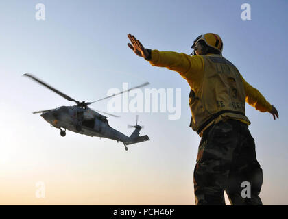 A U.S. Sailor signals to an MH-60 Seahawk helicopter pilot assigned to Helicopter Sea Combat Squadron (HSC) 2 during flight operations aboard amphibious transport dock ship USS San Antonio (LPD 17) in the Atlantic Ocean June 10, 2011. San Antonio was conducting sea trial evolutions. - Stock Photo