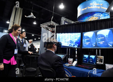 NATIONAL HARBOR, Md. (May 16, 2016) Lauren Burnette, from Space and Naval Warfare Systems Command (SPAWAR) Systems Center Pacific, explains the Battlespace Exploitation of Mixed Reality (BEMR) Lab demo to a visitor at the Office of Naval Research (ONR) exhibit during the 2016 Sea-Air-Space Exposition. BEMR is designed to showcase and demonstrate cutting edge low cost commercial mixed reality, virtual reality and augmented reality technologies and to provide a facility where warfighters, researchers, government, industry and academia can collaborate. - Stock Photo