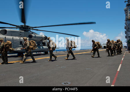 Marines assigned to the 3rd Battalion, 3rd Marine Regiment, board a CH-53E Super Sea Stallion helicopter, assigned to Heavy Marine Helicopter Squadron 463 (HMH-463), on the flight deck of the amphibious assault ship USS Peleliu (LHA 5) during Rim of the Pacific (RIMPAC) Exercise 2014. Twenty-two nations, 49 ships and six submarines, more than 200 aircraft and 25,000 personnel are participating in RIMPAC from June 26 to Aug. 1 in and around the Hawaiian Islands and Southern California. The world's largest international maritime exercise, RIMPAC provides a unique training opportunity that helps  Stock Photo