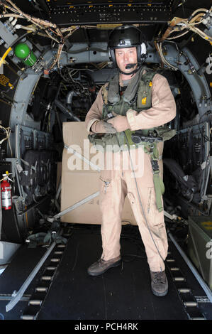 Marine Corps Sgt. Camaron Depue, from Marine Medium Tiltrotor Squadron 162, stands in the aft of an MV-22 Osprey as the aircraft prepares to take off from the U.S. Naval Station Guantanamo Bay airfield. The aircraft, scheduled to fly supplies for Haiti to USS Bataan, is here in support of Operation Unified Response. - Stock Photo