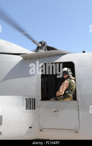Marine Corps Staff Sgt. Jenna Kumdh, from Marine Medium Tiltrotor Squadron 162, looks out the window of an MV-22 Osprey, watching for other aircraft on the flight line at U.S. Naval Station Guantanamo Bay, Jan 24. The aircraft, scheduled to fly to the USS Bataan with supplies for Haiti, is here in support of Operation Unified Response. - Stock Photo