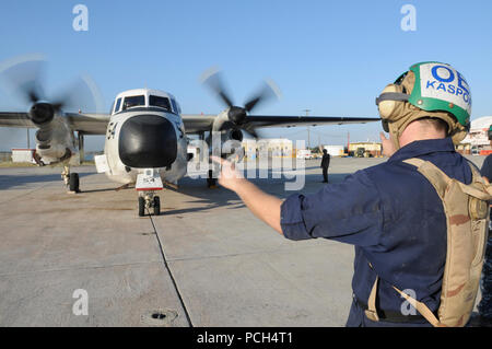 Navy Petty Officer 3rd Class Andrew Kaspor, an aviation electricians mate, marshals the start-up of an engine on a C-2 Greyhound aircraft at U.S. Naval Station Guantanamo Bay, Jan. 24. The aircraft, scheduled to fly missions to Haiti, is here in support of Operation Unified Response. - Stock Photo