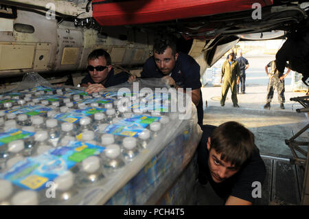 From left, Navy Petty Officers 2nd Class Donald Boylen, an aviation structural mechanic, Justin Leonard, an aviation electronics technician and Jamie Salmon, an aviation warfare flight crewman, push pallets of water onto a C-2 Greyhound aircraft at U.S. Naval Station Guantanamo Bay, Jan. 24. The pallets of water, scheduled for delivery to Haiti, are part of humanitarian assistance in support of Operation Unified Response. - Stock Photo
